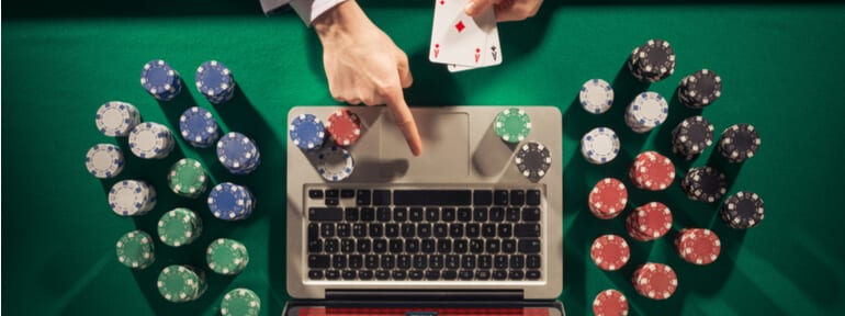 Overhead of hand playing online casino surrounded by casino props