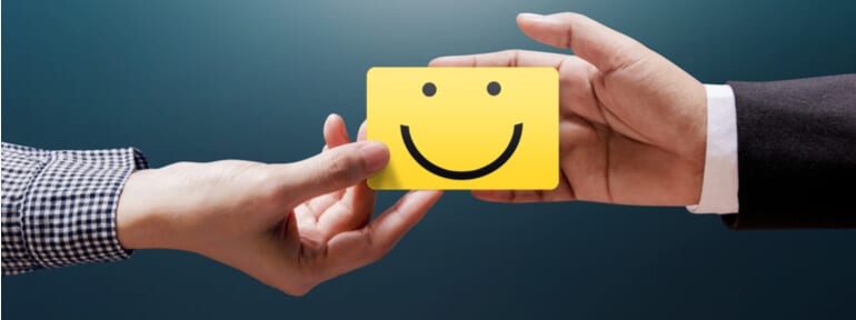 hands exchanging a card with happy face on it
